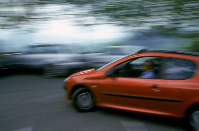 Peugeot 206 orange entrain de rouler sur un parking